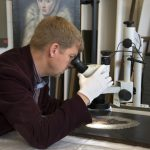 Colour photograph of Examining El Greco's Portrait of a Gentleman with a stereomicroscope, copyright of CSG CIC Glasgow Museums Collection
