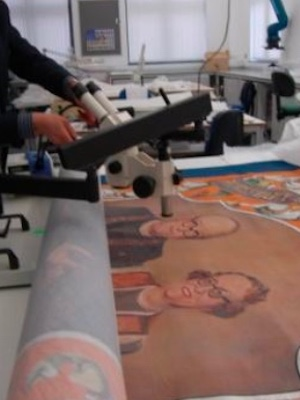 Colour photograph showing a researcher using microscopy to examine a painted textile banner