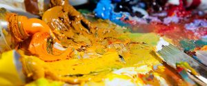 Colour photograph showing a mix of bright colour paints, paint tubes and artist brushes