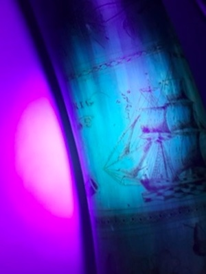 Colour image of a detail from a carved powder horn, circa. 1838, from The Royal Highland Fusiliers Museum, Glasgow under UV light (Courtesy of Georgia Tooley)