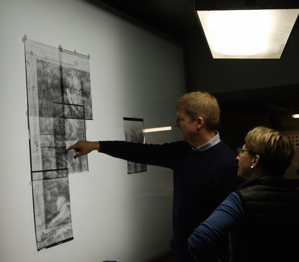 Colour photograph showing Mark Richter and Hilary Macartney viewing an X-ray of a portrait of Philip II by Alonso Sánchez Coello (Photo courtesy of Ela Gorska-Wiklo)